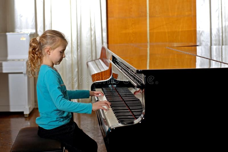 La fille joue le piano, fin, blanc et noir noir de clavier avec les clés blanches dans la salle de concert image libre de droits