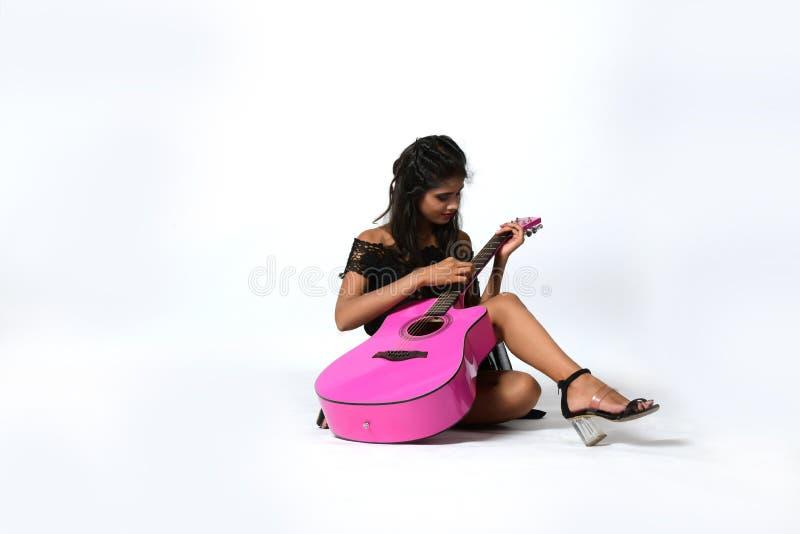 La fille joue une guitare rose se reposant sur le plancher photographie stock libre de droits