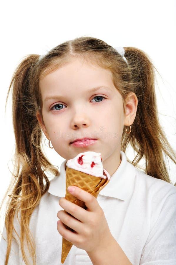 La fille joyeuse d'enfant mange de la glace photo stock