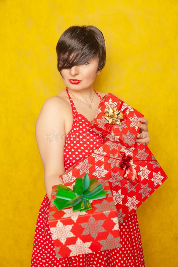 La fille joyeuse douce dans une rétro robe rouge de point de polka se tient avec trois boîtes de cadeaux dans ses mains et sourir photos libres de droits