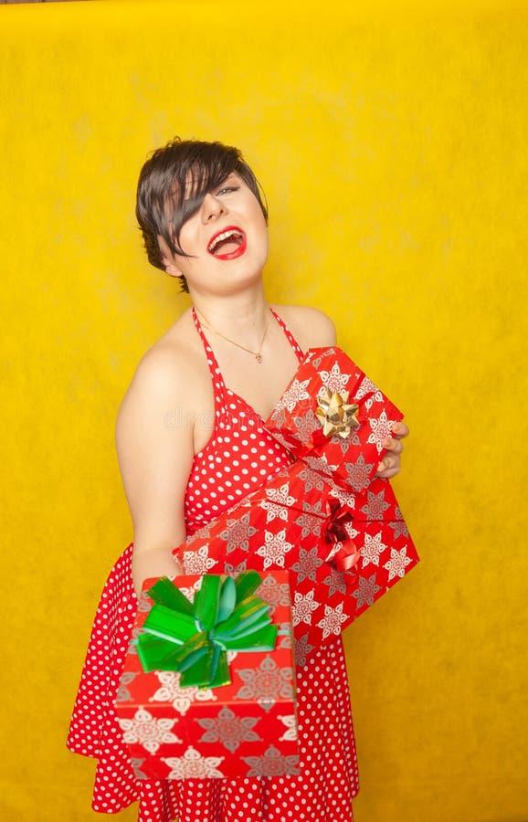 La fille joyeuse douce dans une rétro robe rouge de point de polka se tient avec trois boîtes de cadeaux dans ses mains et sourir photo libre de droits