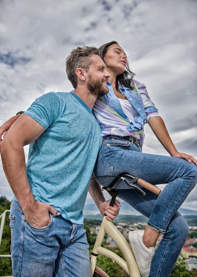 La fille l'aime la monte sur le guidon La fille s'asseyent sur le guidon de son v?lo Le macho barbu d'homme monte l'amie sur son  image libre de droits