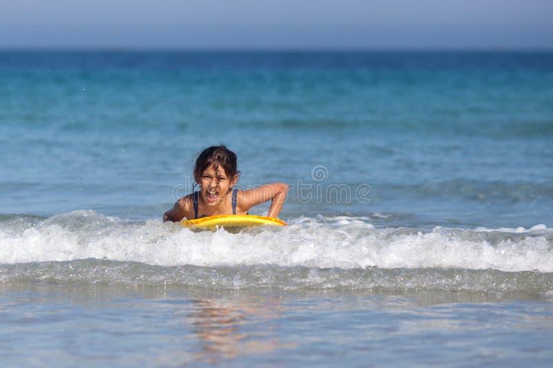 La fille a l'amusement avec la planche de surfing image stock