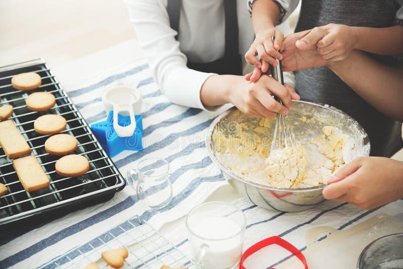 La fille, l'enfant et la jeune femme asiatiques préparent la pâte images stock