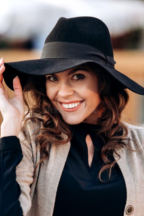 La fille ?l?gante habill?e dans un col roul? noir, un cap beige, une jupe courte ?l?gante et un chapeau noir avec les cloches lar image stock