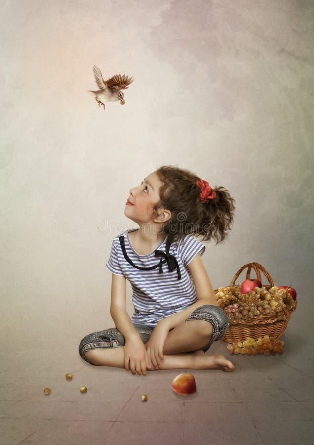 La fille, l'oiseau et les raisins photographie stock