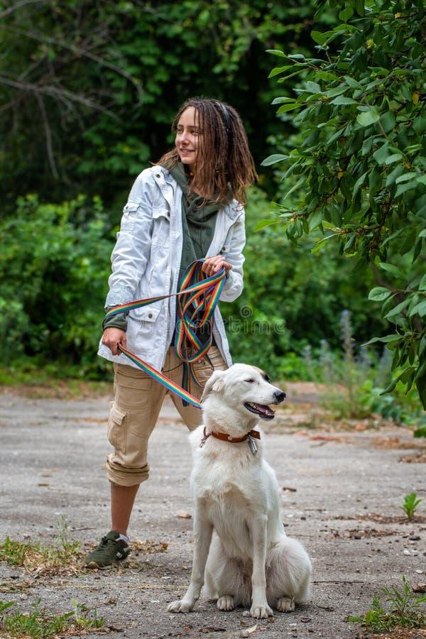 La fille latine avec des dreadlocks garde un chien sur une laisse ?t? Fond brouill? par vert Communication avec l'animal photographie stock