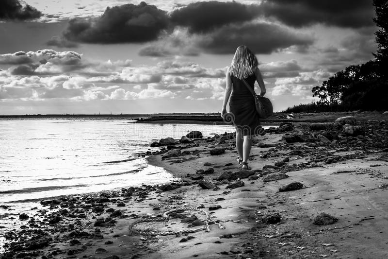 La fille le long de la plage est partie Coeur abandonné en sable Photographie noire et blanche Lumières dramatiques photographie stock