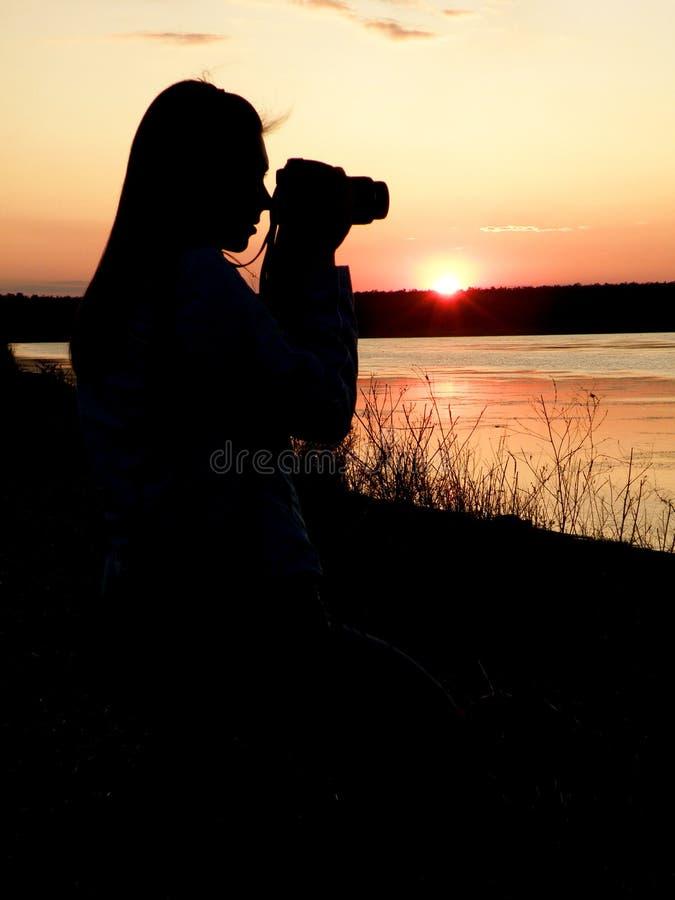 La fille le photographe contre un coucher du soleil photo stock