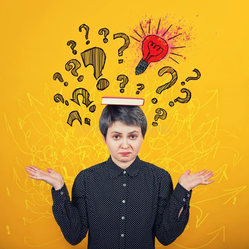 La fille a les marques d'interrogation et une ampoule au-dessus de tête Questions et concept d'id?e Trouvez la solution aux probl photographie stock