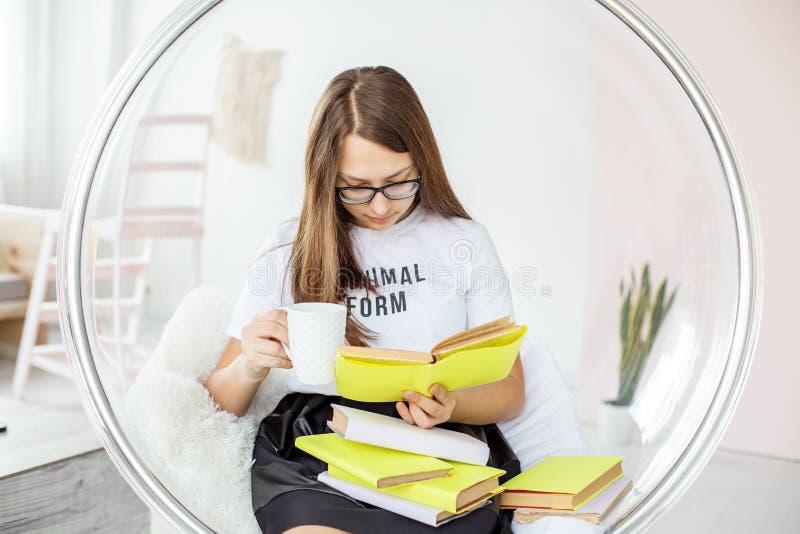 La fille lit avec enthousiasme un livre avec des verres Thé potable Concept d'éducation, passe-temps et étude et jour de livre du photos stock