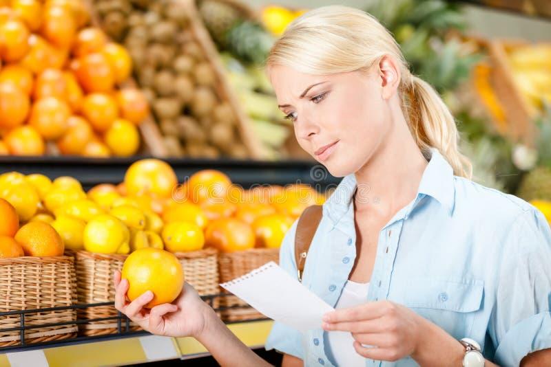 La fille lit la liste d'achats et remet une orange images libres de droits