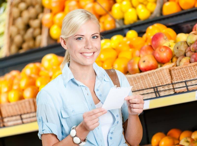 La fille lit la liste d'achats près de la pile de fruits images stock