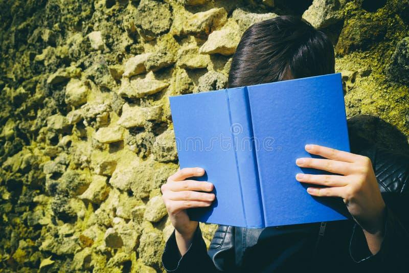 La fille lit un livre près d'un mur image libre de droits