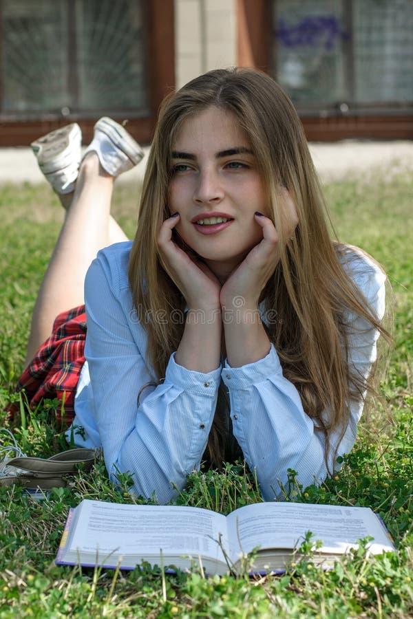 La fille lit un livre tout en se trouvant sur l'herbe images stock