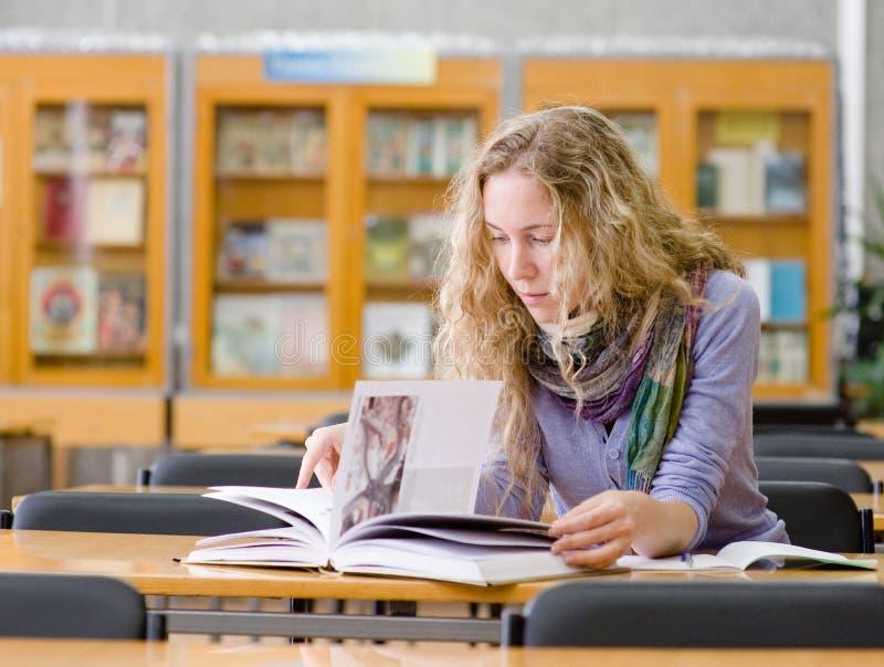 La fille a lu le livre dans la bibliothèque photo libre de droits