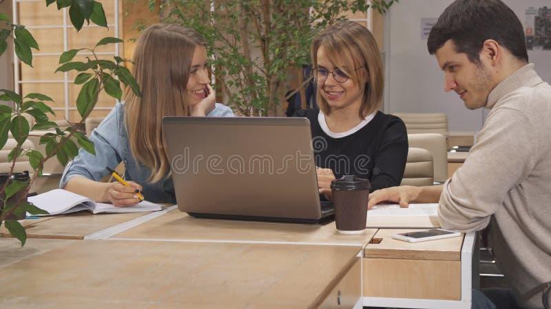 La fille lui dit des collègues de regarder son ordinateur portable photographie stock