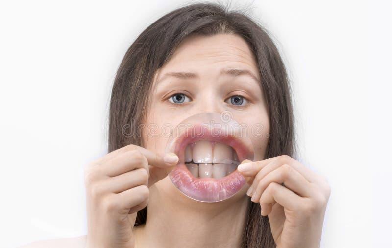 La fille lui montre des lèvres et des dents par la grande loupe images stock