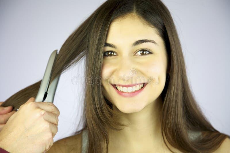 La fille lui obtient le sourire repassé par cheveu photographie stock libre de droits