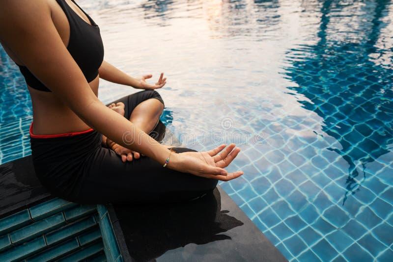 La fille médite au coucher du soleil en Thaïlande près de la piscine image stock