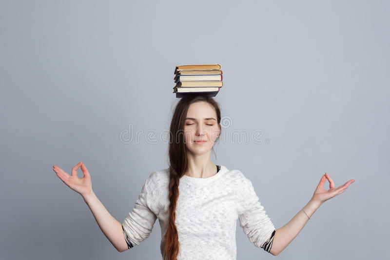 La fille médite avec une pile des livres sur la tête images libres de droits