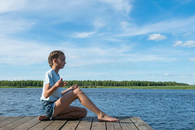 La fille médite en nature par le lac un beau jour ensoleillé image libre de droits