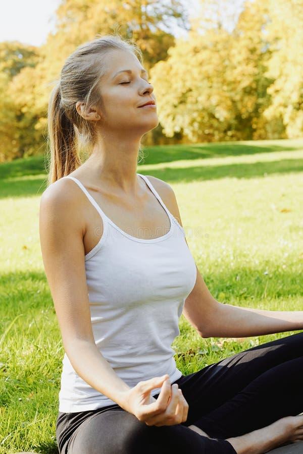 La fille médite tout en pratiquant le yoga dehors en parc photographie stock libre de droits