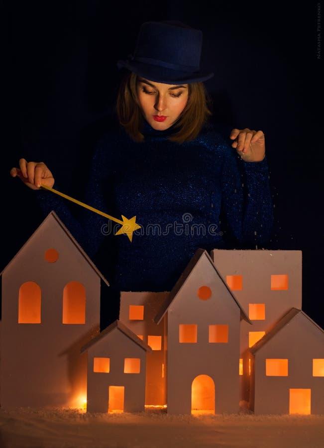 La fille magique dans le chapeau jette la neige sur la ville avec une baguette magique magique photographie stock libre de droits