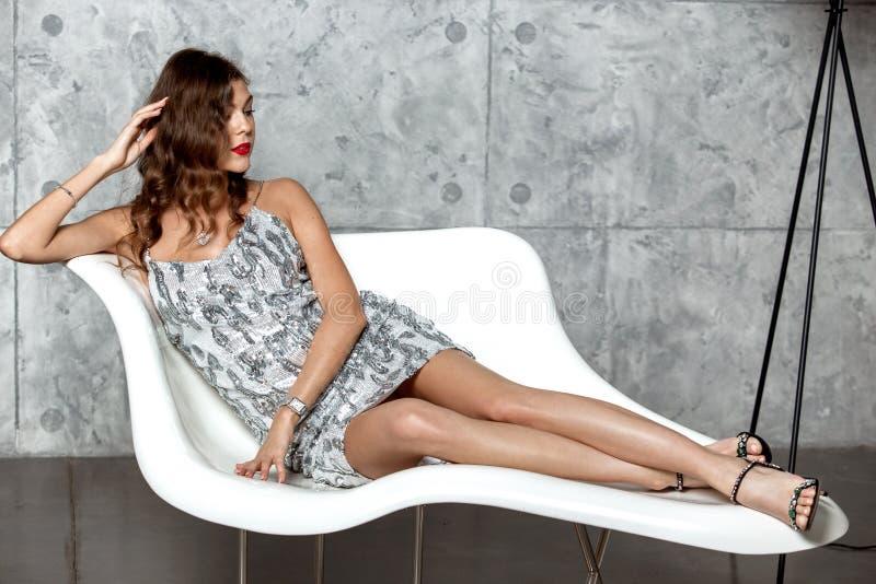 La fille magnifique de brune dans une robe ?galisante grise merveilleuse s'?tend dans un fauteuil blanc ?l?gant contre le mur gri image libre de droits