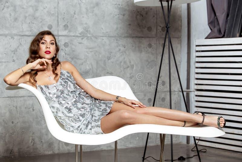 La fille magnifique de brune dans une robe ?galisante grise merveilleuse s'?tend dans un fauteuil blanc ?l?gant contre le mur gri photos libres de droits