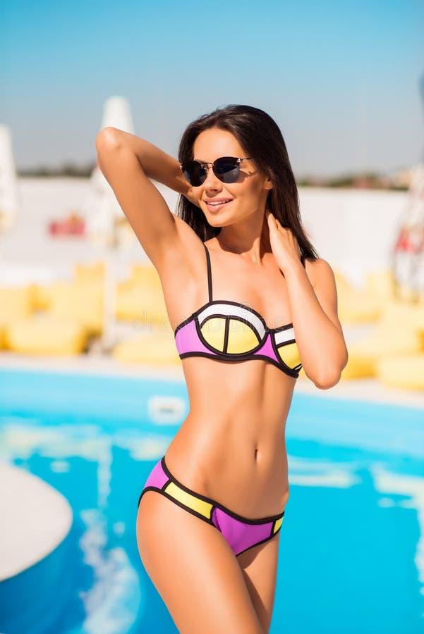 La fille magnifique de brune mince sexy en verres de soleil se tient prêt t images libres de droits