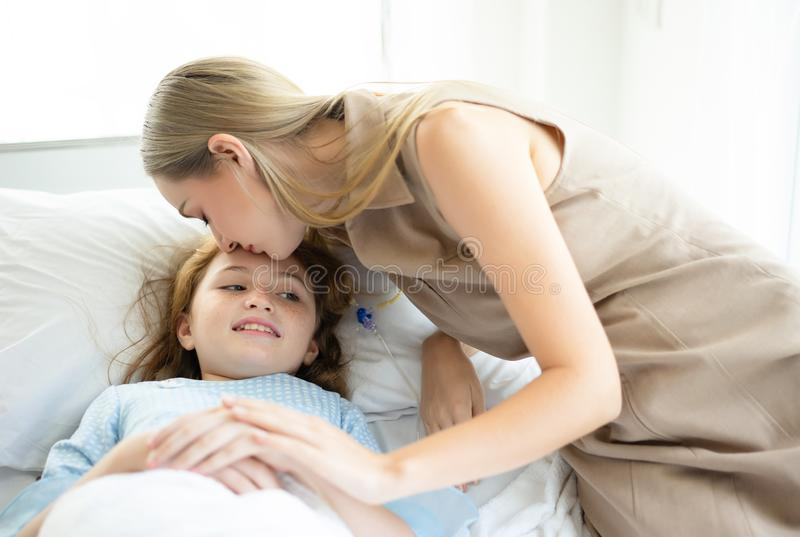 La fille malade d'enfant avec la pose dans le lit à lier de main d'hôpital et de mère et la maman l'embrassent pour soutenir la f images stock
