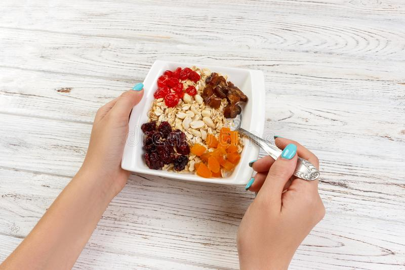 La fille mange la farine d'avoine avec des fruits secs Fond en bois foncé de petit déjeuner utile et sain, vue supérieure photos stock