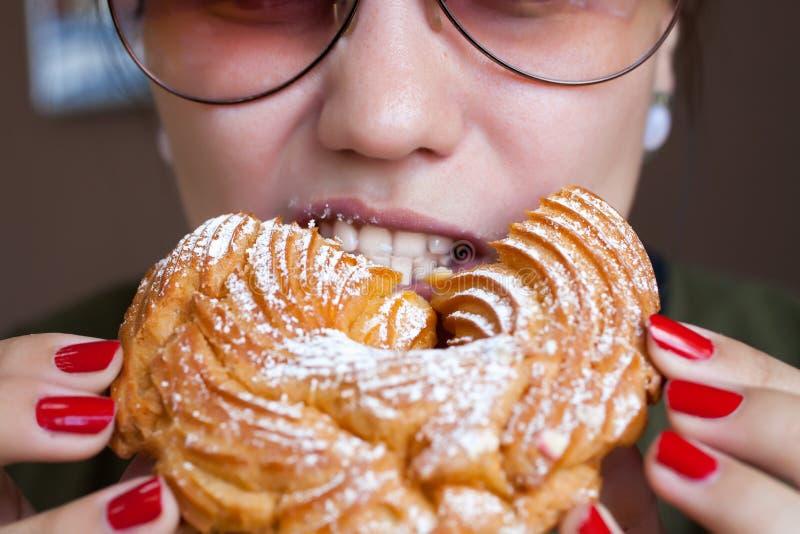 La fille mange un anneau de crème anglaise - un dessert russe traditionnel photos libres de droits