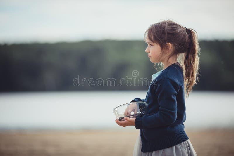 La fille mangeant des myrtilles d'un bol en verre image libre de droits