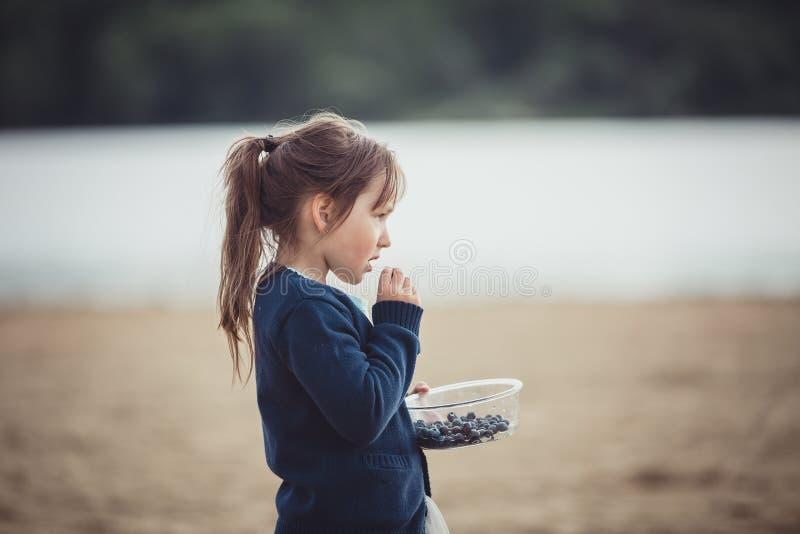 La fille mangeant des myrtilles d'un bol en verre photos stock