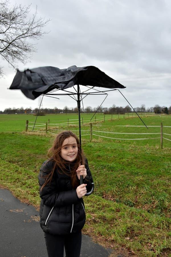 La fille marche avec le parapluie cassé par la tempête image stock