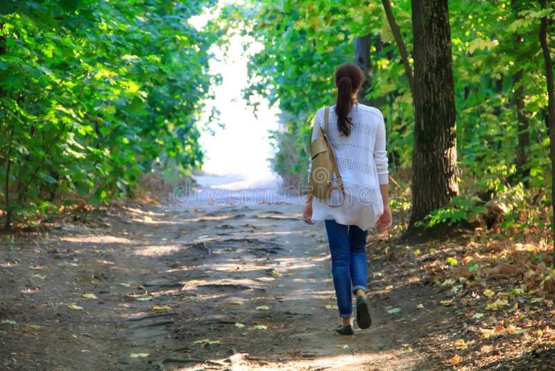 La fille marche le long du chemin dans les bois à la lumière photos stock