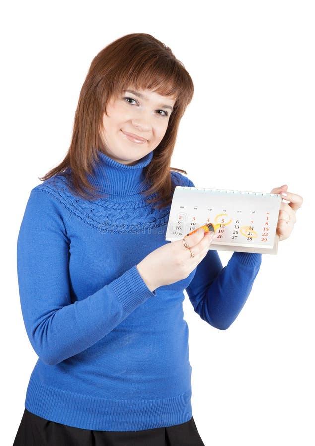 La fille marque un jour sur à un calendrier photo stock