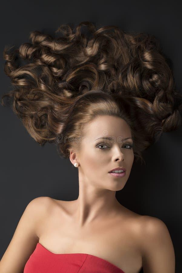 La fille menteuse sexy avec le long cheveu bouclé examine la lentille photographie stock libre de droits