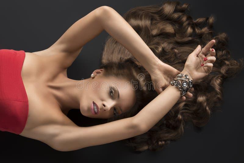 La fille menteuse sexy avec le longs cheveu bouclé et bras a augmenté sur la tête images libres de droits