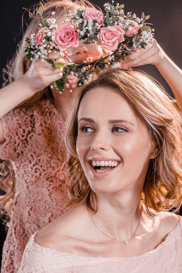 La fille mettant des fleurs tressent sur la tête du ` s de mère sur le noir image stock
