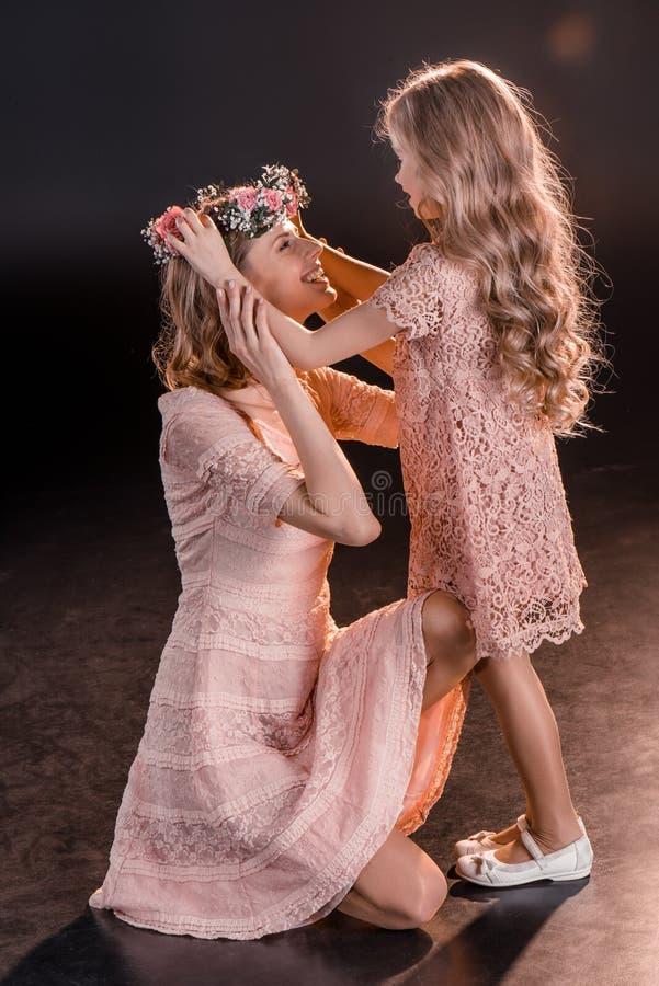 La fille mettant des fleurs tressent sur la tête du ` s de mère sur le noir photos libres de droits