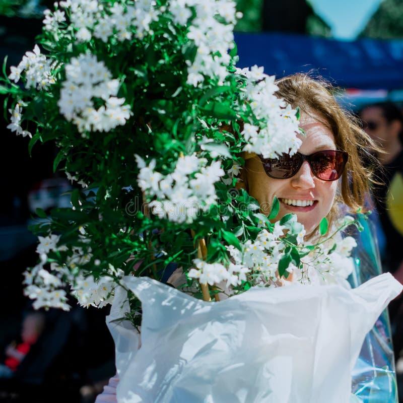 La fille mignonne achète des fleurs photos libres de droits