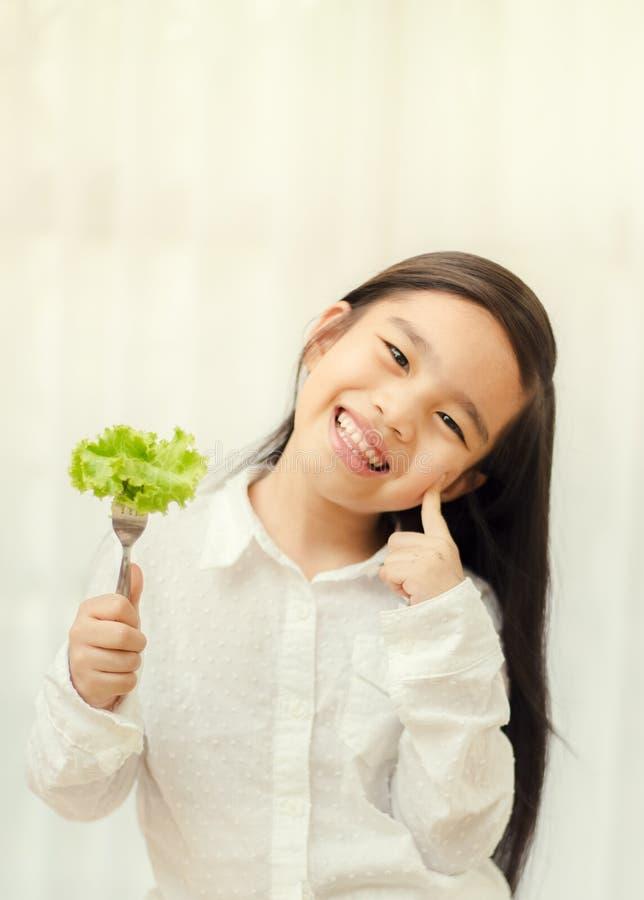 La fille mignonne asiatique mange de la salade fraîche, concept sain de consommation photographie stock libre de droits
