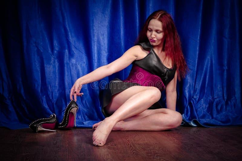 La fille mignonne avec les cheveux rouges dans une robe et un corset en cuir s'assied sur le plancher nu-pieds et apprécie de bel photo stock
