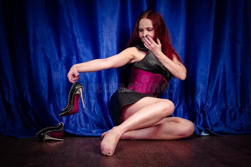 La fille mignonne avec les cheveux rouges dans une robe et un corset en cuir s'assied sur le plancher nu-pieds et apprécie de bel image stock