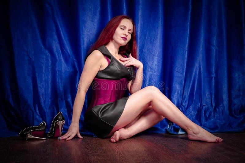 La fille mignonne avec les cheveux rouges dans une robe et un corset en cuir s'assied sur le plancher nu-pieds et apprécie de bel photographie stock libre de droits