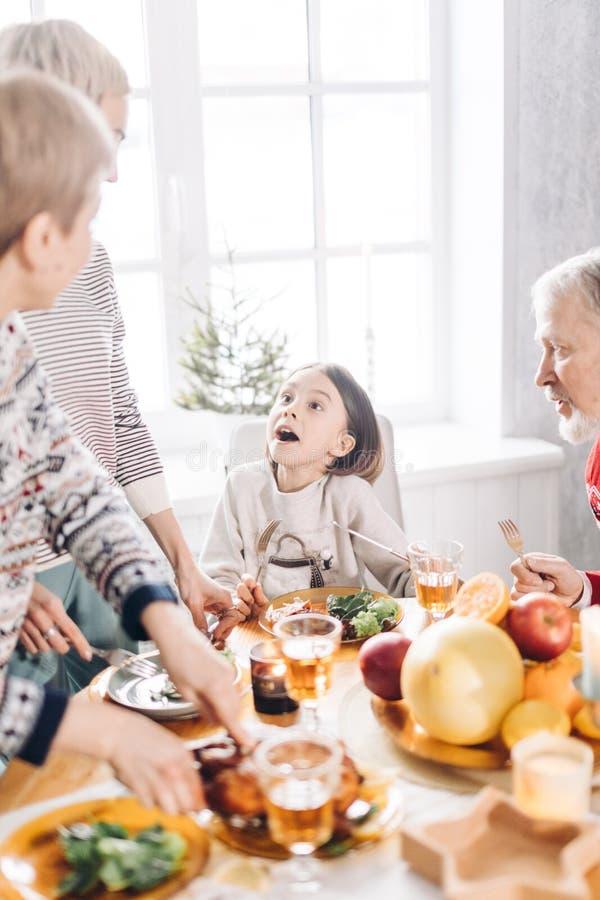 La fille mignonne curieuse parle avec ses parents tout en havving le dîner image libre de droits