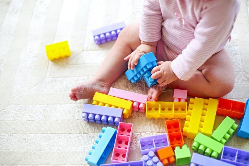 La fille mignonne d'enfant en bas âge ayant l'amusement avec le jouet bloque se reposer sur la carpe photographie stock